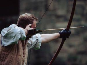 Traditioneller Bogenschütze schießt mit Primitivbogen ohne Pfeilauflage